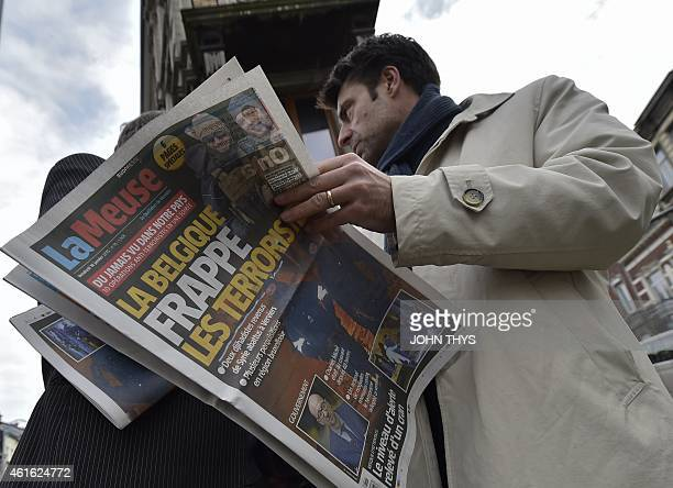 A journalist reads a newspaper about the Belgian police raid near Colline street in Verviers eastern Belgium on January 16 after police shot dead two...