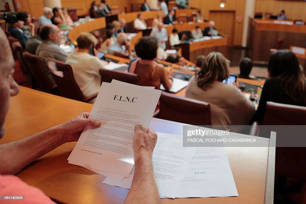 A journalist reads a report from the FLNC during a session at the Corsican Assembly about radical islamism in Ajaccio on the French Mediterranean...