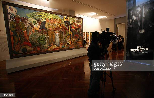 A journalist records the paiting 'Gloriosa Victoria' created by Mexican artist Diego Rivera during a presentation for the press at the Fine Arts...