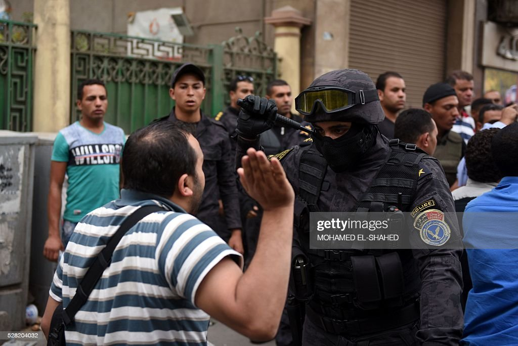 A journalist scuffles with a policeman during a protest to demand the sacking of the interior minister on May 4, 2016 outside the Journalists' Syndicate headquarters in Cairo, after an unprecedented police raid to arrest two reporters. Egyptian police stormed the headquarters of the journalists' association in central Cairo on May 1, 2016 and arrested two journalists, Amr Badr and Mahmud el-Sakka, for incitement to protest. / AFP / MOHAMED