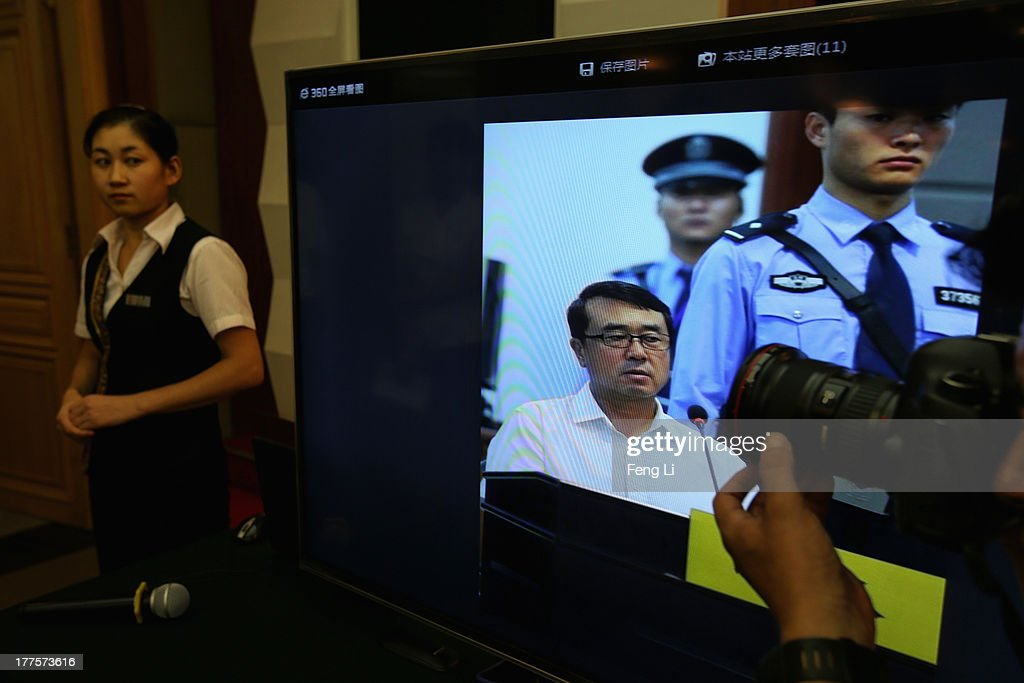 A journalist shoots a picture of former police chief Wang Lijun as he gives evidence on the third day of the trial of disgraced politician Bo Xilai at the Jinan Intermediate People's Court on August 24, 2013 in Jinan, China. Ousted Chinese politician Bo Xilai is standing trial on charges of bribery, corruption and abuse of power for a third day. Bo Xilai made global headlines last year when his wife Gu Kailai was charged and convicted of murdering British businessman Neil Heywood.
