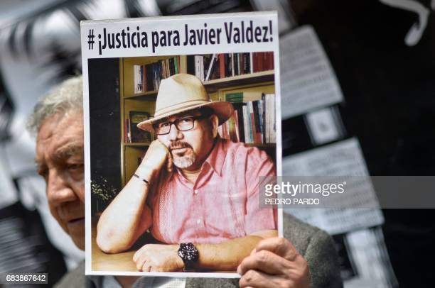 A journalist shows a picture of Mexican journalist Javier Valdez murdered on the eve during a protest by journalists in Mexico City on May 16 2017...