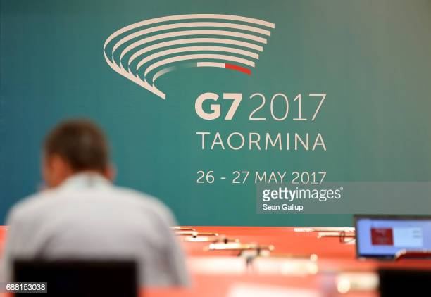 A journalist sits near a G7 summit banner in the media center for the G7 Taormina summit on the island of Sicily on May 25 2017 in Giardini Naxos...