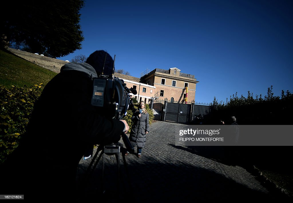 A journalist speaks on February 19, 2013 outside the convent of Mater Ecclesiae (Mother of the Church) at the Vatican City State. The building will host Pope Benedict XVI, offering him a substantial four-story modern home complete with contemporary chapel, garden and a roof terrace looking out from a rise dominated by the Holy See's TV transmission tower. Pope Benedict XVI began a week-long spiritual retreat out of the public eye on Monday ahead of his resignation on February 28 with the field of candidates to succeed him still wide open. AFP PHOTO/ Filippo MONTEFORTE