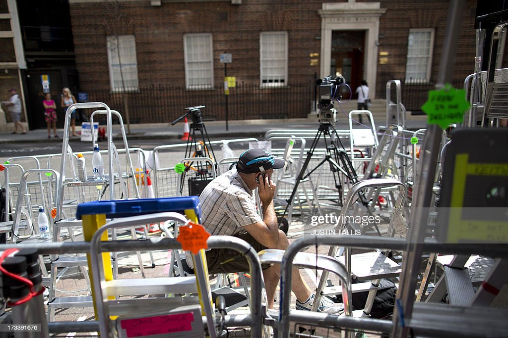 A journalist speals on his mobile phone as he sits amid media stepladders outside the Lindo Wing of St Mary's hospital in London, on July 13, 2013, where Prince William and his wife Catherine's baby will be born. Britain's royal family and the world's media are on tenterhooks awaiting the birth of Prince William and wife Catherine's first child, a baby who will one day be king or queen of Britain and a diverse group of commonwealth countries. AFP PHOTO / JUSTIN TALLIS