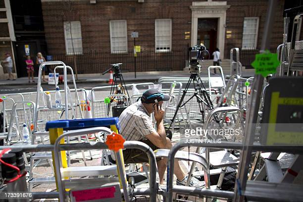 A journalist speals on his mobile phone as he sits amid media stepladders outside the Lindo Wing of St Mary's hospital in London on July 13 where...