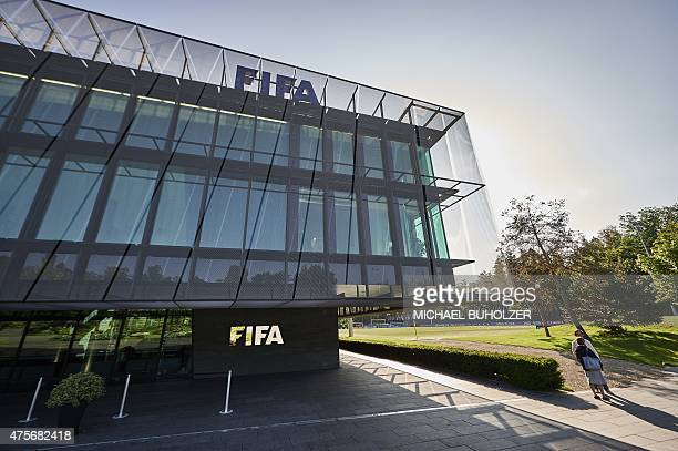 A journalist stands in front of the FIFA headquarters on June 3 2015 in Zurich Blatter on June 2 2015 resigned as president of FIFA as a mounting...