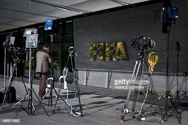 A journalist stands in front of the FIFA logo at the FIFA headquarters on September 25 2015 in Zurich The controversial 2022 World Cup in Qatar will...