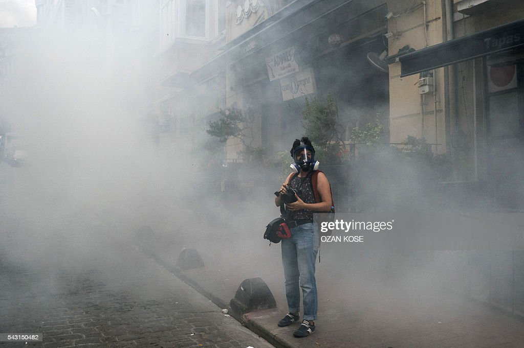 A journalist stands in tear gas demonstrators gathered for a rally staged by the LGBT community on Istiklal avenue in Istanbul on June 26, 2016. Riot police fired tear gas and rubber bullets to disperse protesters defying a ban on the city's Gay Pride parade. Authorities in Turkey's biggest city had banned the annual parade earlier this month citing security reasons, sparking anger from gay rights activists. KOSE