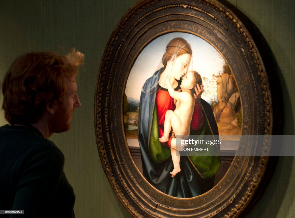 A journalist takes a close up look at 'The Madonna and Child' by Fra Bartolommeo January 24, 2013 at Christie's in New York. The painting is one of the works scheduled to be auctioned during Old Masters week, January 26-31, 2013. AFP PHOTO/DON EMMERT