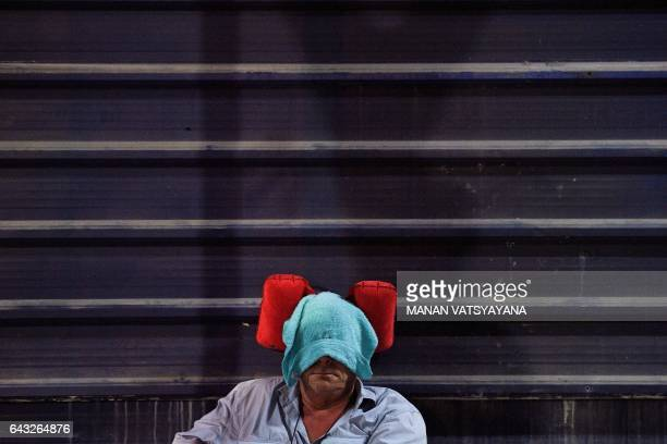 A journalist takes a nap outside the forensic wing at Hospital Kuala Lumpur in the early hours of February 21 where the body of a North Korean man...