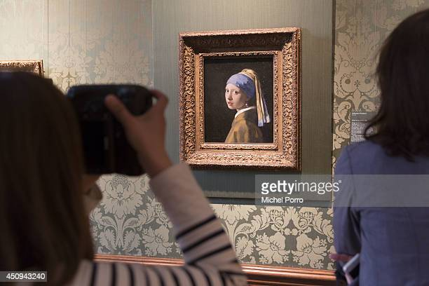 A journalist takes a photo of Johannes Vermeer's 'Girl with a Pearl Earring' in the Vermeer Room in the Mauritshuis Museum on June 20 2014 in The...