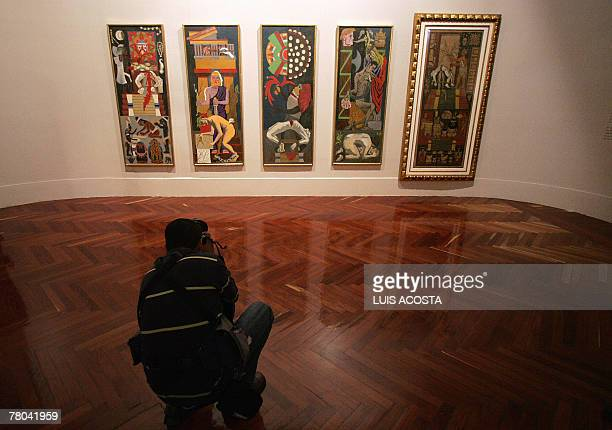 A journalist takes a picture of the paitings 'Religiones' created by Mexican artist Diego Rivera during a presentation for the press at the Fine Arts...
