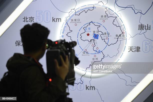 A journalist takes a video in front of a map of Beijing and Heibei province during a tour arranged by the press center for the 19th Communist Party...