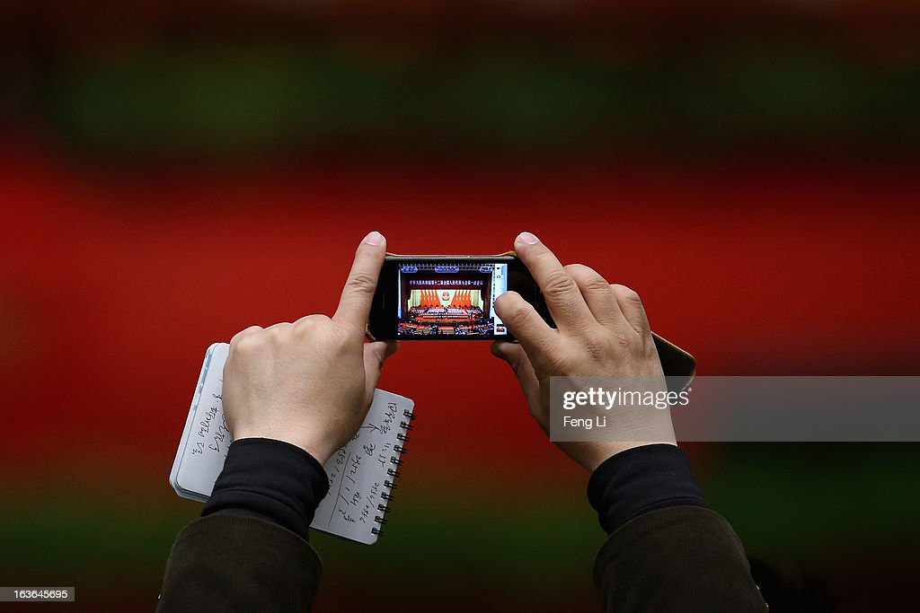 A journalist takes photos with smart phone during the fourth plenary meeting of the National People's Congress (NPC) at the Great Hall of the People on March 14, 2013 in Beijing, China. Xi Jinping, general secretary of the Communist Party of China Central Committee, was elected President of the People's Republic of China and Chairman of the Central Military Commission on Thursday.