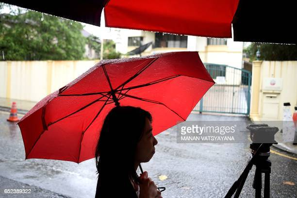 A journalist takes shelter from rain outside the North Korean embassy in Kuala Lumpur on March 12 2017 Malaysia hopes to open negotiations with North...