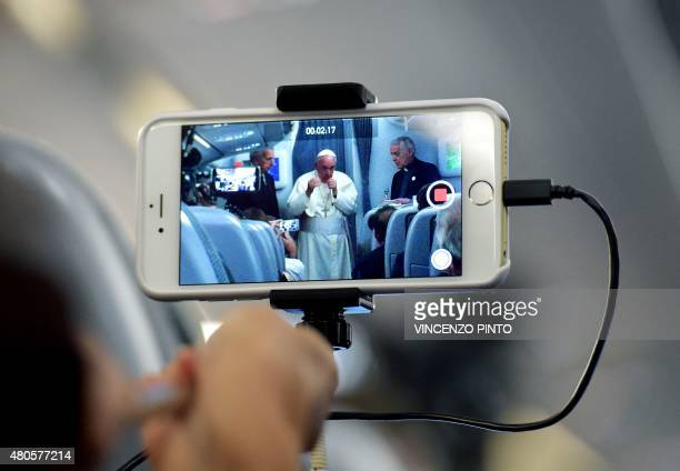 A journalist takes with his mobile phone a picture of Pope Francis during a press conference on July 13 onboard a plane on his way back to Rome from...