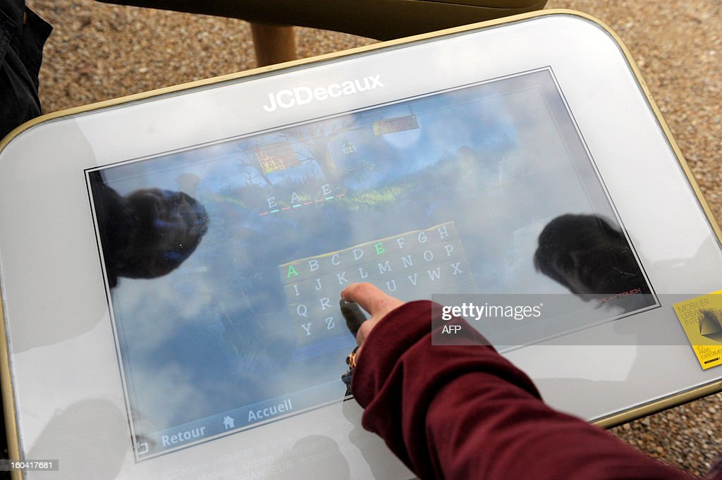 A Journalist tries a 'table Play', a video game table prototype designed by French Mathieu Lehanneur and proposed by the global outdoor advertising leader JCDecaux during its presentation in a Paris' garden on January 31, 2103. Forty Table Play's prototypes are tested on the Parisian territory as part of the 'smart urban street furniture' (Mobilier Urbain Intelligent) project bid launched by Paris city hall.