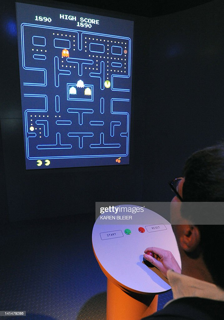 A journalist tries out the original version of Pac-Man inside the exhibition 'The Art of Video Games,' March 15, 2012 at the Smithsonian's American Art Museum in Washington, DC. The Art of Video Games is one of the first exhibitions to explore the forty-year evolution of video games as an artistic medium, with a focus on striking visual effects and the creative use of new technologies. The exhibition runs March 16-September 30, 2012. AFP PHOTO/Karen BLEIER