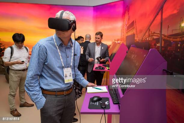 A journalist tries virtual reality glasses during the presentation of Los Angeles 2024 Olympic bid's showroom in Lausanne on July 12 2017 The...