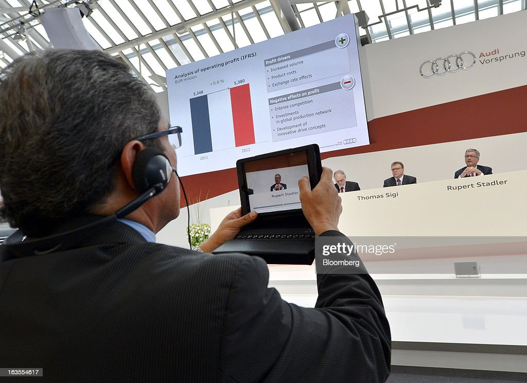 A journalist uses a small laptop computer to photograph Rupert Stadler, chief executive officer of Audi AG, as he speaks during the company's earnings news conference at the Audi AG headquarters in Ingolstadt, Germany, on Tuesday, March 12, 2013. Audi AG, the world's second-biggest luxury carmaker, is aiming for a 'slight' increase in revenue this year and reaching an operating margin at the upper end of its long-term target corridor, helped by sales of compact SUVs and the new A3 sedan. Photographer: Guenter Schiffmann/Bloomberg via Getty Images
