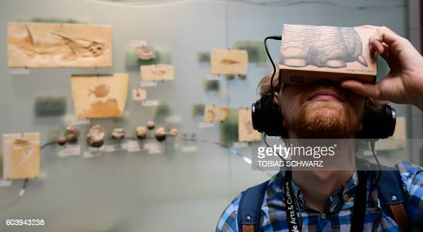 A journalist uses a smartphone equipped with a socalled 'Google Cardboard' mount to use it as a VR device for trying out a new offer developed by...