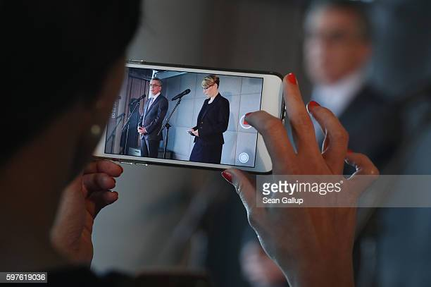 A journalist uses an iPhone to film German Interior Minister Thomas de Maiziere and Tina Kulow Facebook Corporate Communications Director for...