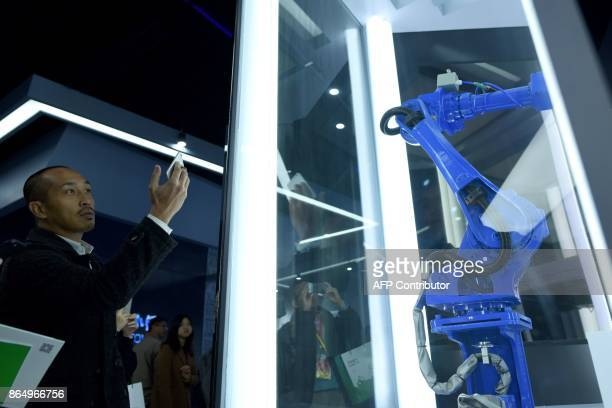 A journalist uses his mobile phone to take a picture of a robot arm at an exhibition center during a tour arranged by the press center for the 19th...