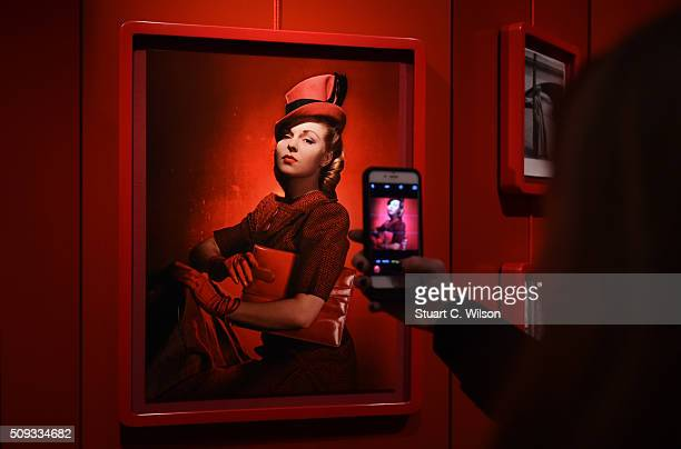 A journalist uses their phone to take a picture at the press preview for 'Vogue 100 A Century of Style' exhibiting the photographs that has been...