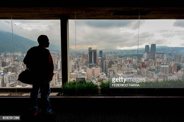 A journalist waits for the start of a press conference at the Central Bank of Venezuela in Caracas on December 7 2016 The BCV on Wednesday presented...