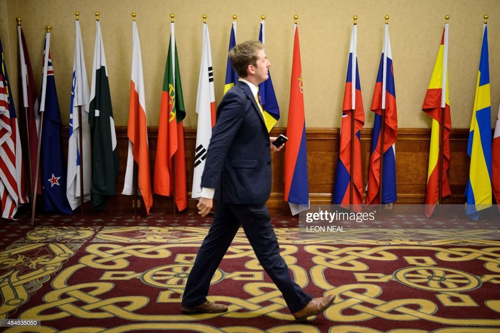 A journalist walks past a display of NATO flags at the Celtic Manor Hotel in Newport, South Wales, on September 3, 2014, on the eve of hosting the NATO Summit. Some 67 world leaders will be attending the NATO summit taking place on September 4-5, for crisis talks on Russia's role in the war in Ukraine and the Islamic State (IS). AFP PHOTO/POOL/LEON NEAL