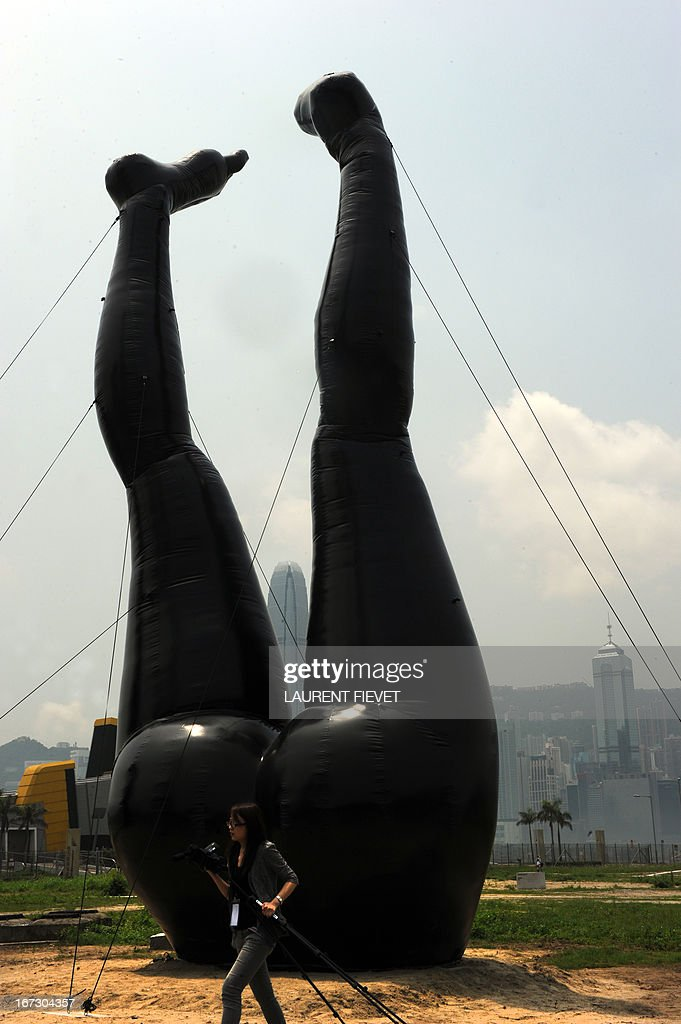 A journalist walks past a sculpture by Hong Kong artist Tam Wai Ping titled 'Falling into Mundane World' during a press preview of the Mobile M+: Inflation! exhibition in Hong Kong on April 24, 2013. Mobile M+: Inflation! presented six giant inflatable sculptures installed next to M+, Hong Kong's future museum for visual culture, and will open to the public from 25 April – 9 June.