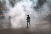 A journalist walks through smoke after violence broke out between proRussian activist and progovernment supporters during a rally and march on April...