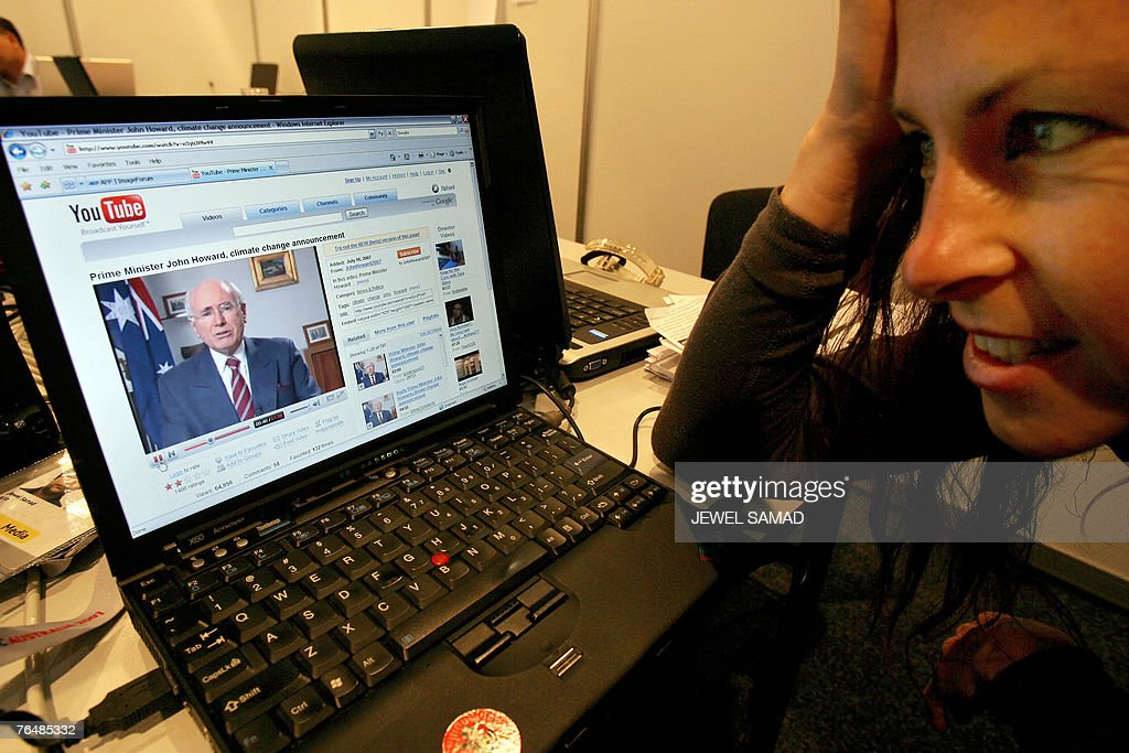 A journalist watches Australian Prime Minister John Howard making a foray into the YouTube videosharing in Sydney 03 September 2007 Howard made a...
