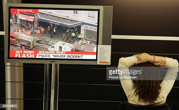 Journalist watches breaking news on the station blasts in central London on a TV screen in the Press work arena in Gleneagles July 7 2005 Blasts have...