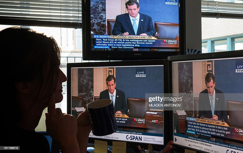 A journalist watches C-SPAN TV on computer screens showing US Senator Ted Cruz (R-TX) on September 25, 2013 in Washington,DC. Most US senators expect to pass a stopgap spending bill this week, but one lawmaker is so against it he took to the Senate floor -- for 19 hours and counting. Few knew that Senator Ted Cruz would still be engaged in his talkathon, much less even awake, on Wednesday morning to oppose the temporary budget. But such is his fierce opposition to President Barack Obama's signature health care law, whose funding is part of the bill, that he held the Senate floor through the night, delivering one of the longest Senate speeches since precise record-keeping began in 1900. The conservative first-term lawmaker was voicing what he said is America's deep discontent for the law known as 'Obamacare,' and aimed to unite Republicans in opposition to passing a spending bill that does not defund the health care law.