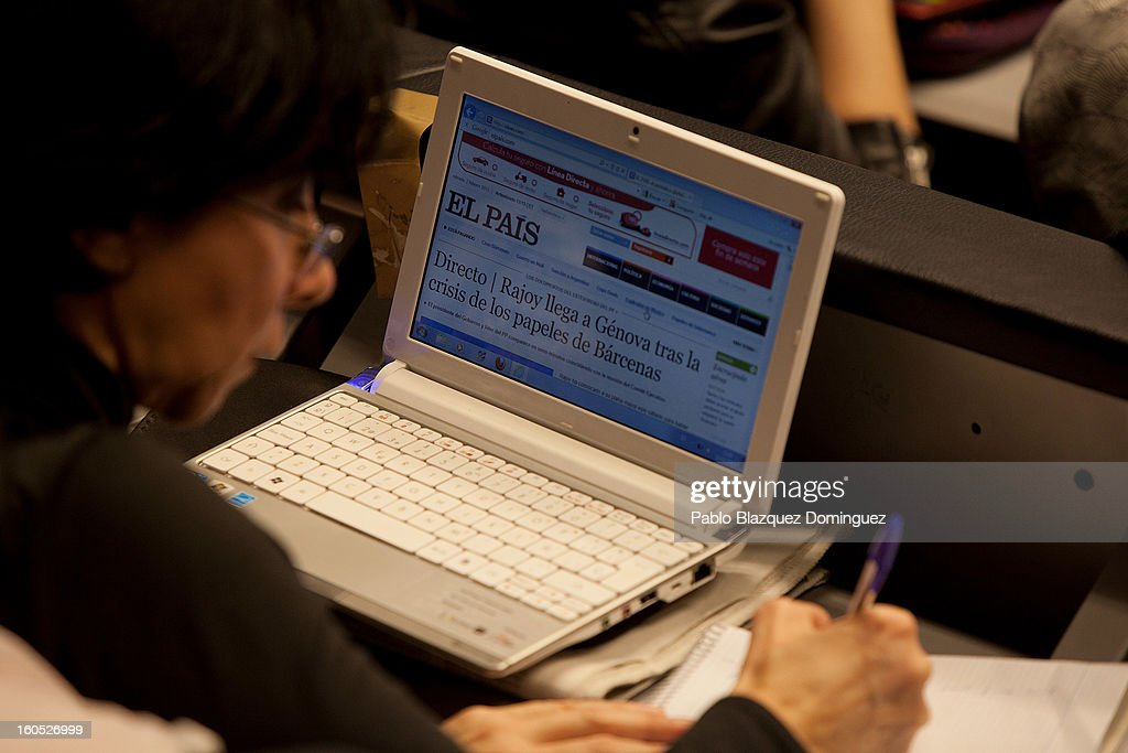 A journalist watches Mariano Rajoy's conference on a tv screen as she has the 'El Pais' website open inside the Press Room during the PP national executive comitee in the PP Headquarters on February 2, 2013 in Madrid, Spain. Spanish reports alleged Rajoy and other conservative politicians received regular payments from a previously undisclosed account run by the treasurers of his Popular Party from 1990 to 2008.