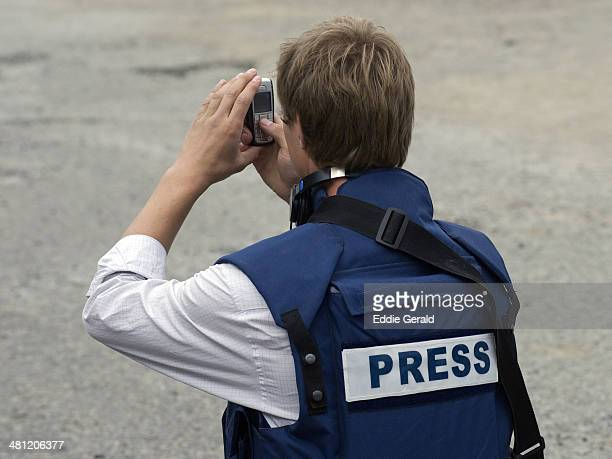 A journalist wearing a flack jacket taking photos with a mobile phone in a war zone