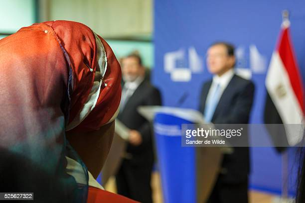 A journalist with an orange head scarf listens to European Commission President Jose Manuel Barroso right and the Egyptian President Mohamed Morsi...