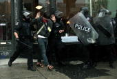 A journalist with visible credentials is arrested by riot police as rain pours down at the conclusion of the G20 Summit June 27 2010 in Toronto...