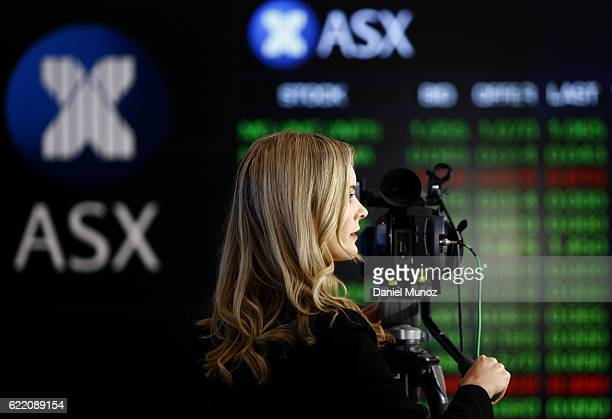 A journalist works in front of the main board of the Australian Securities Exchange building on November 10 2016 in Sydney Australia Americans voted...