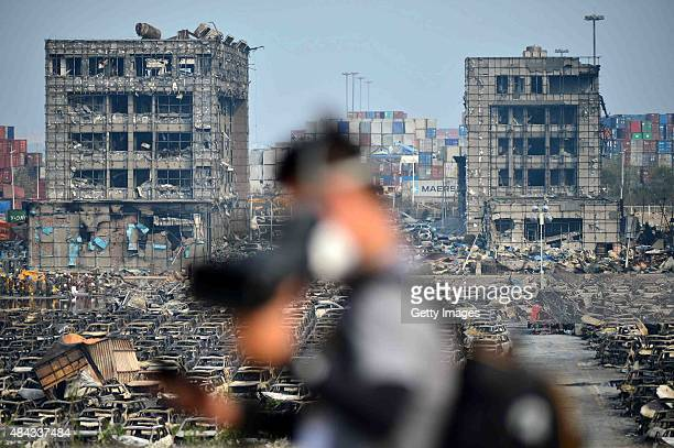 A journalist works on a bridge near the blast site during the aftermath of the warehouse explosion on August 17 2015 in Tianjin China The death toll...