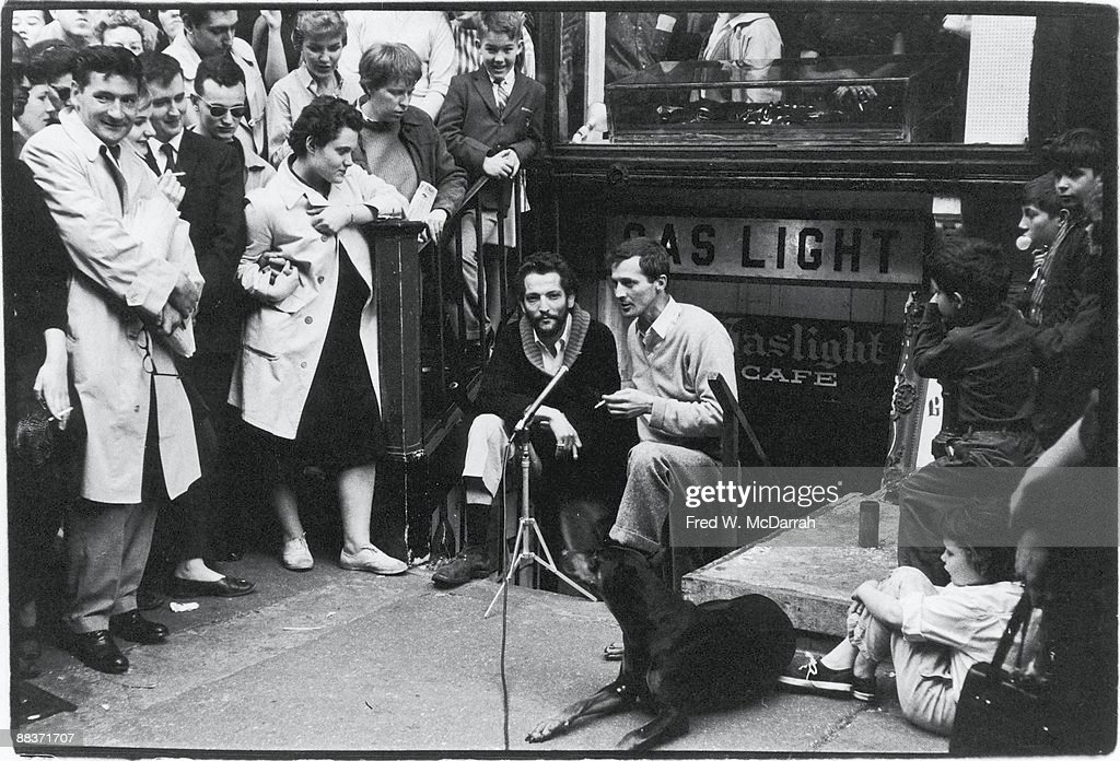 Journalist Yaakov Kohn and writer cafe owner John Mitchell stand on the steps that lead down to Mitchell's Gaslight Cafe a coffee house and nightclub...