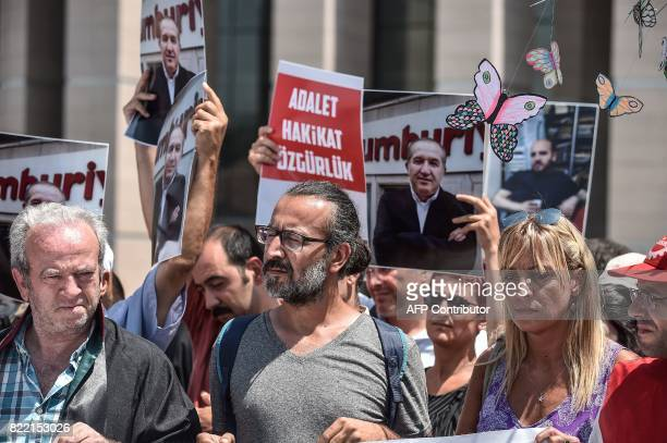 Journalists and activist hold pictures of jailed journalists and a placard that reads 'Justicerealityfreedom'during a demonstration in front of...