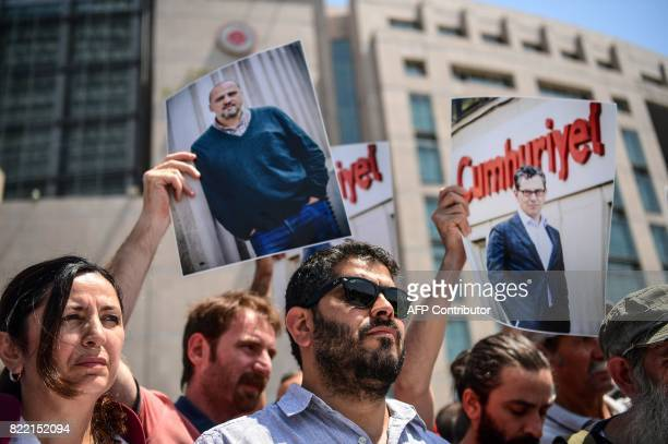 Journalists and activists hold pictures of jailed journalists during a demonstration in front of Istanbul's courthouse on July 25 2017 Seventeen...
