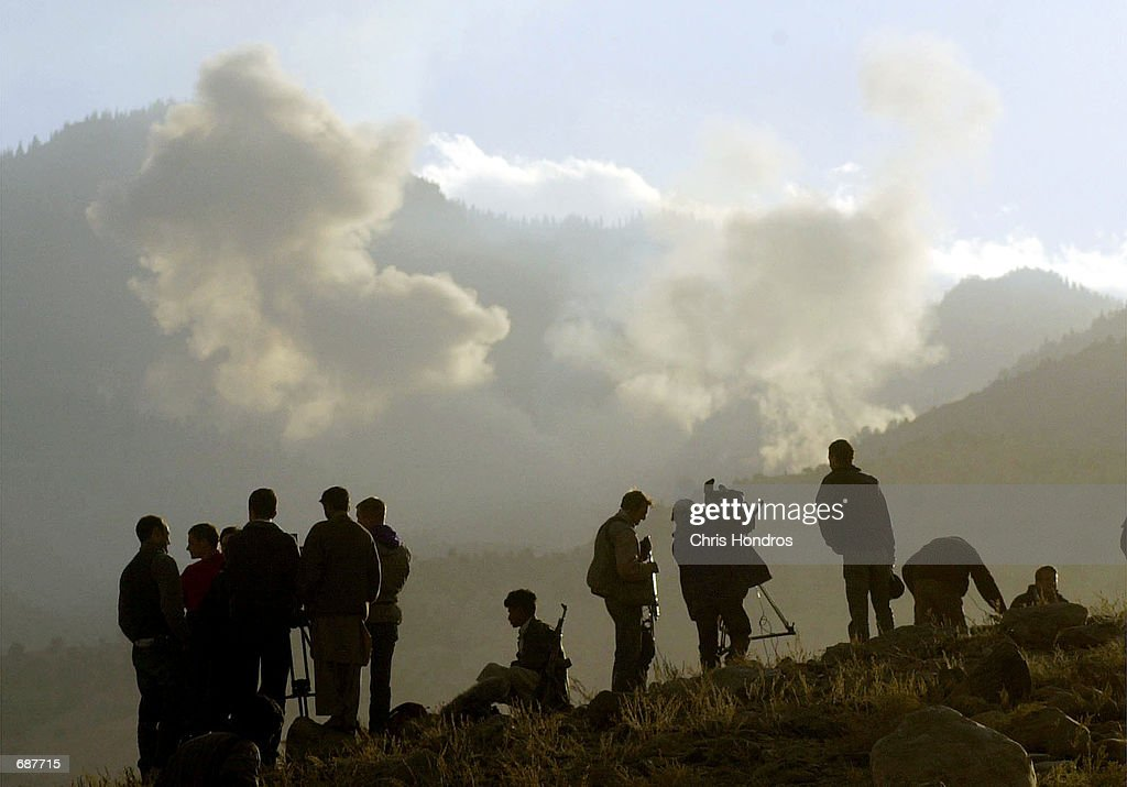 Journalists and antiTaliban soldiers watch plumes rise from bombs dropped on AlQaeda positions by American bombers December 15 2001 in the Tora Bora...