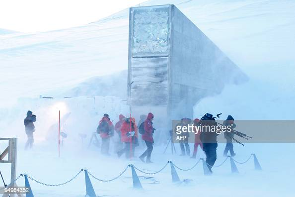 Journalists and cameramen walk under a gust of cold wind near the entrance of the Svalbard Global Seed Vault that was officially opened near...