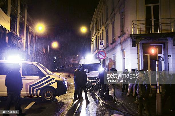 Journalists and local residents stand near police vehicles as police set a large security perimeter in the city center of Verviers on January 15...