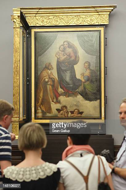 """Journalists and museum employees admire the """"Sistine Madonna"""" painting by 16th century Italian painter Raphael moments after gallery assitants hung..."""