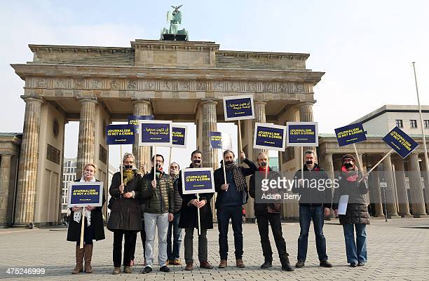 Journalists and other demonstrators protest in front of the Brandenburg Gate against the detaining of Al Jazeera reporters currently in jail in Cairo...